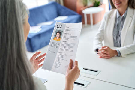 Employer hr manager holding cv resume at job interview meeting. 免版税图像