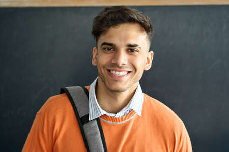 Portrait of young happy latin student standing in classroom looking at camera.