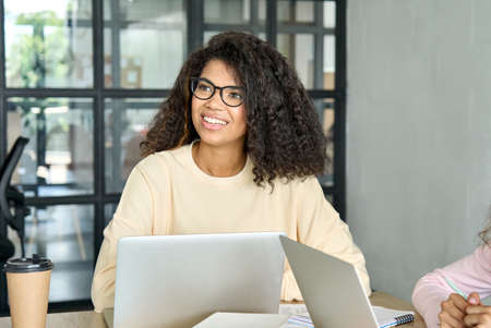 African american young female student sitting using laptop at modern office. 免版税图像