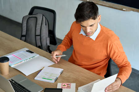 Indian student looking at book at desk in classroom writing notes using pc. 免版税图像