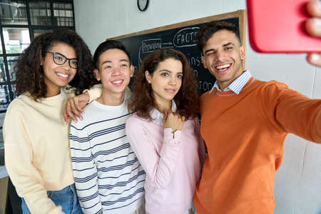 Four happy multiracial students making selfie on black board background.