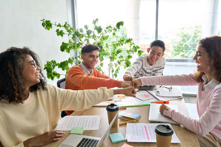 Four cheerful happy startup creative team together in office giving fist bump. 免版税图像