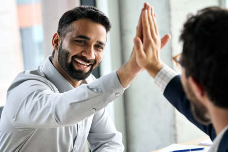 Two happy international businessmen giving high five at meeting board room.