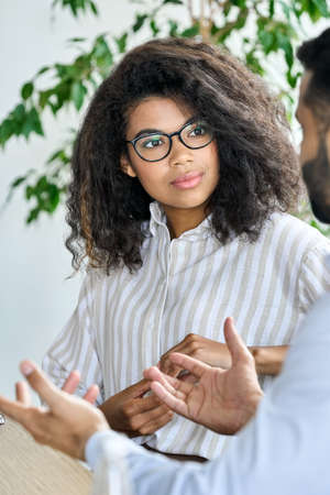 Female African American manager listening to Indian ceo mentor leader.