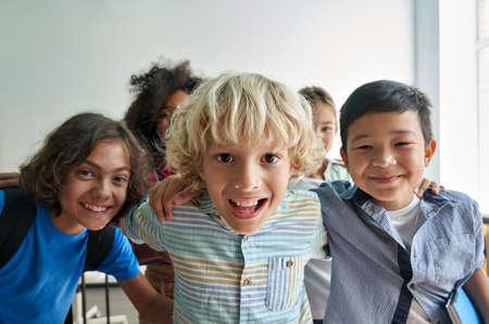 Portrait of happy cheerful smiling diverse kids having fun in classroom. Standard-Bild