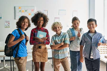 Portrait of happy cheerful smiling diverse schoolchildren in classroom.