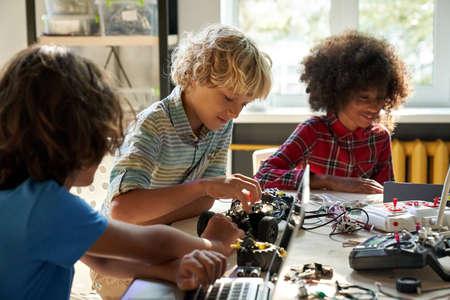 Diverse schoolkids building robotic technologies at STEM educational class.