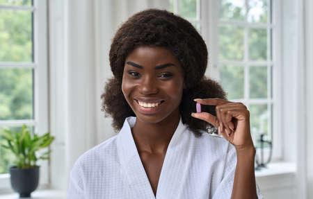 Young pretty happy smiling black girl holding beauty pill. Headshot portrait. Standard-Bild