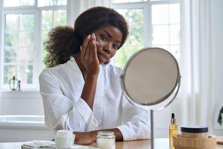 Young happy black girl applying facial cream in front of mirror in bathroom.