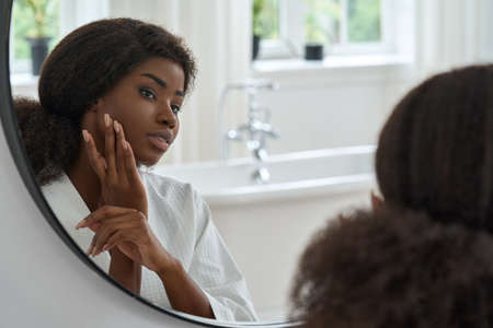Attractive black young woman touching face skin looking in mirror.