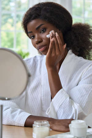 Young black girl applying moisturizing cream in front of mirror in bathroom.