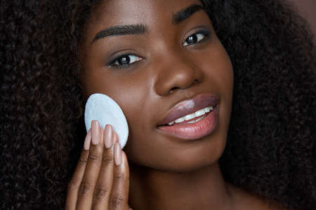 Black young woman holding cotton pad removing face make up with makeup remover.