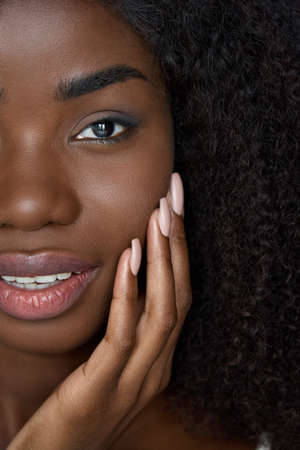 Happy black young woman touching flawless face skin, closeup vertical portrait.