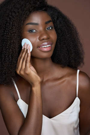 Beautiful happy black girl purifying skin with cotton pad. Skincare concept.