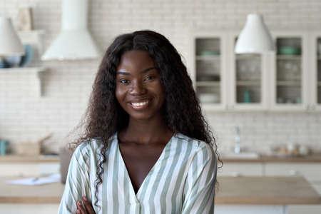 Headshot portrait of young black woman looking at camera indoors. Standard-Bild