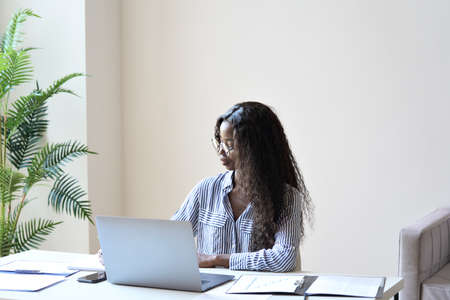 Young concentrated mixed race businesswoman at desk with papers and laptop.