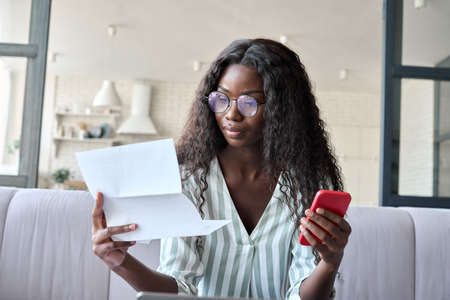 Young serious African American businesswoman reading letter using cellphone.