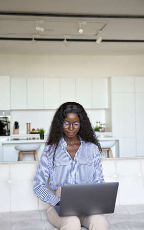 Young smart mixed raced black female student sitting typing using laptop.