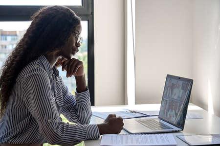 Young mixed race black businesswoman at desk having online webinar using pc. Standard-Bild