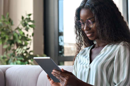 African American smiling girl in glasses sits on sofa at home holding tablet.
