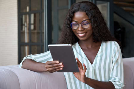 Afro American smiling young girl sitting on sofa at home holding tablet device.
