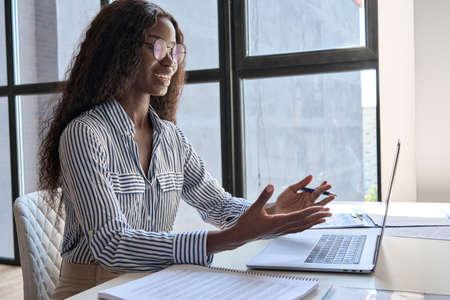 Young smiling black businesswoman at desk having online meeting using laptop. Standard-Bild