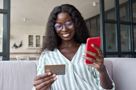 Young black smiling woman holding credit card using cell phone at home.