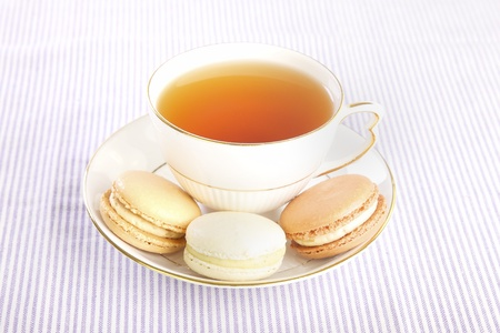 Delicate porcelian cup of tea and macaroons, Bed and Breakfast display Stock Photo