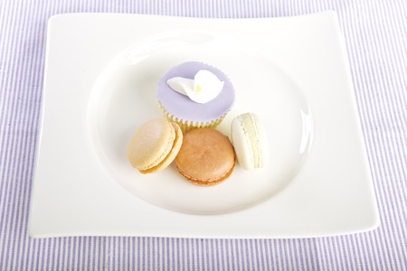 Cupcake and macaroons displayed on a plate photo