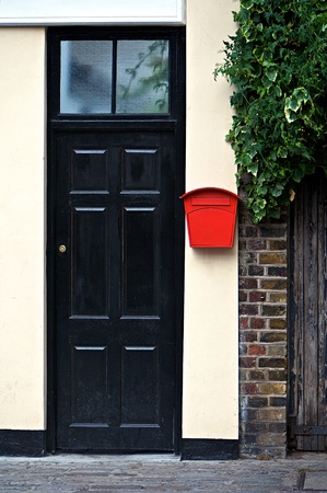 Black door front with red letter box photo