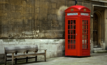British Phone Booth With Weathered Wooden Bench Stock Photo