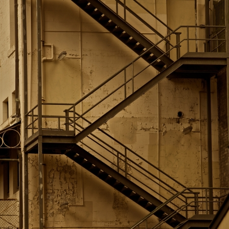 escape: Metal Fire Escape Stairs on the Side of a Textured Building Sepia
