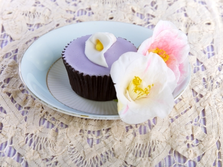 Cupcake and flowers displayed on a plate photo