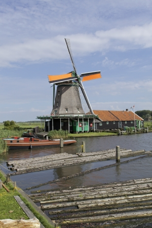 wind powered building: Very old authentic windmills in a row in Zaandam or Zaanse Schans, Neterhlands, Holland, Europe Very popular with the tourists and old are of Netherlands Stock Photo