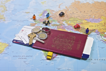 British Passport flight ticket and personal belongings displayed on a world map  Travel and vacation photo