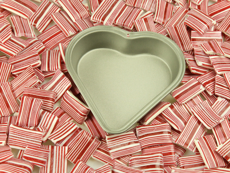 tin: Heart tin, surrounded by candy and sweets Stock Photo