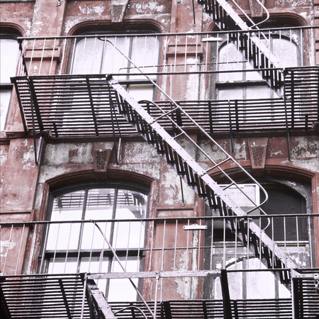Weathered red  building with fire escape stairs in New York City, USA