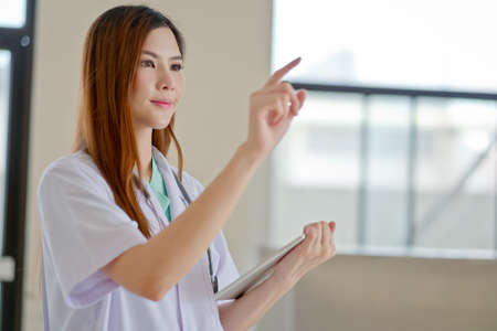 beautiful womb: Happy smiling young beautiful female doctor showing blank area for sign or copyspace