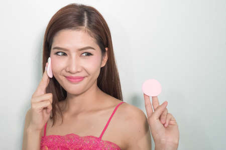 powder puff: Young woman applying foundation on face with powder puff