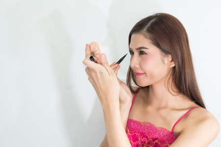 eyeliner: Beautiful model applying eyeliner closeup on eye