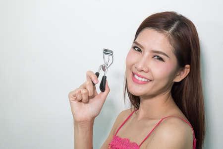 curler: Woman Using Eyelash Curler Stock Photo