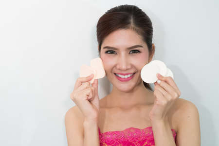 powder puff: Young woman applying powder on her face with powder puff.