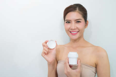 skincare products: Portrait of Beautiful Young Woman looking at Camera with skincare products Stock Photo