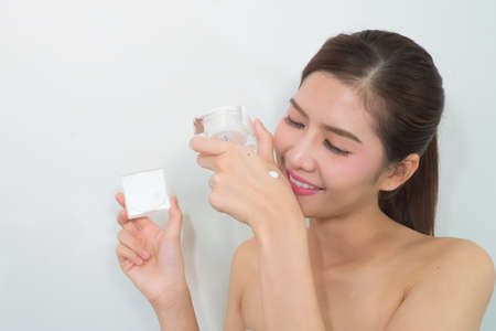 doctor holding gift: A beautiful asian woman using a skin care product, moisturizer or lotion.
