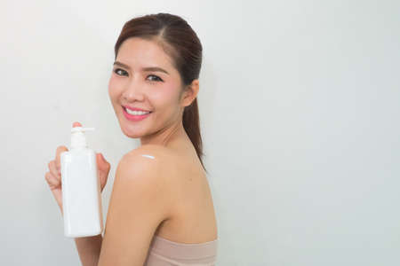 doctor holding gift: Portrait of Beautiful Woman looking at Camera with body lotion Stock Photo