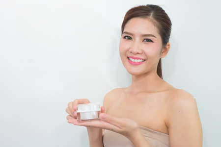 doctor holding gift: beautiful woman applying cosmetic cream