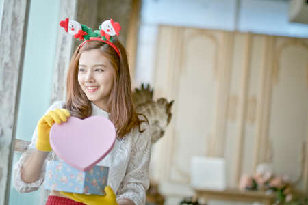 girl with winter clothes holding a Christmas gift box
