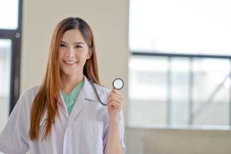 Happy smiling young beautiful female doctor showing blank area for sign or copyspace,The photos from inside the building. Stock Photo