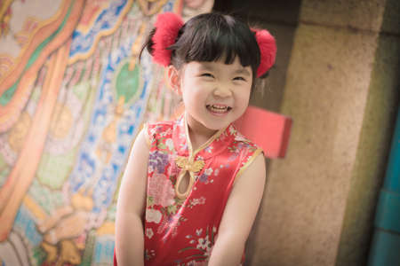 Cute girl wearing red Chinese suit,Photos provided by background ambience China .