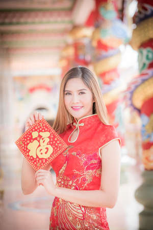 Asian woman in chinese dress holding couplet Happy  (Chinese blessing word) with chinese temple background.